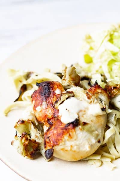 Artichoke Chicken, Pasta, and Salad on a plate