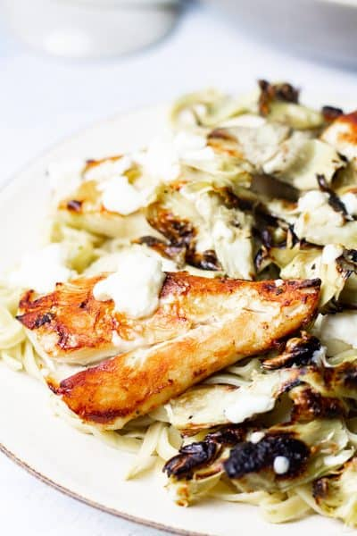 Serving plate of broiled artichoke chicken with feta and fresh pasta