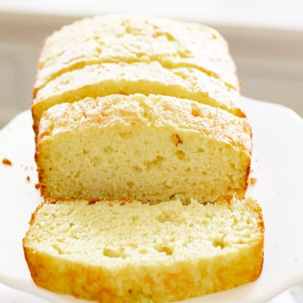 sliced 4-ingredient lemon zucchini bread on a white cake stand