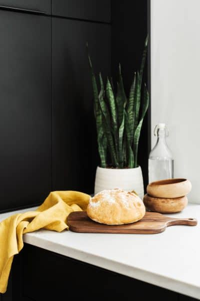 fresh baked bread, a yellow towel, plant, and bowls on a kitchen counter