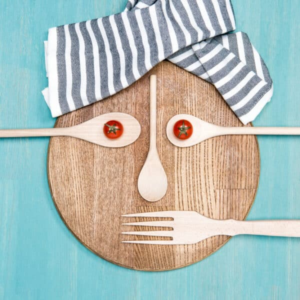 top view of wooden cooking utensils with tomatoes in form of face on kitchen board