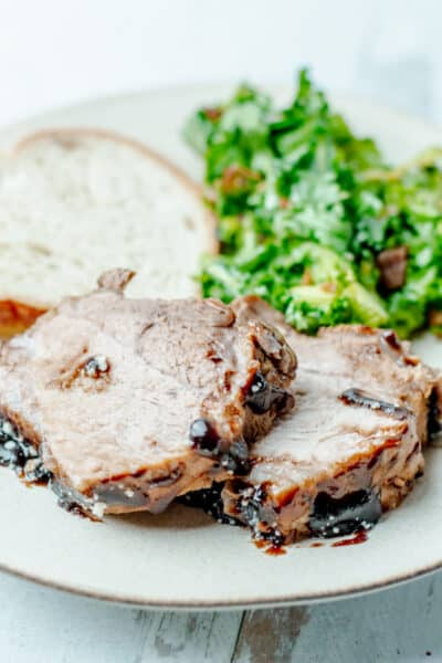 Slices of instant pot parmesan balsamic pork roast on a plate with salad and bread