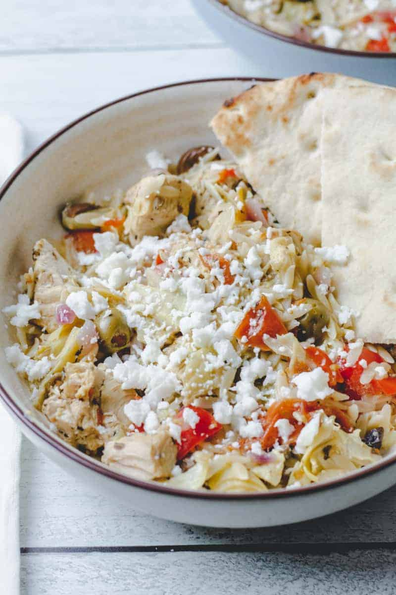 table with two bowls of instant pot greek chicken orzo and pita bread