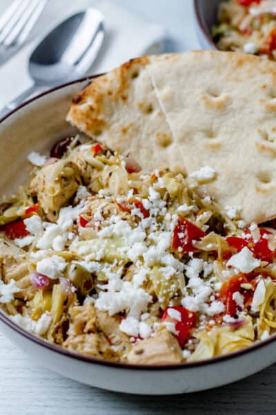 close up of greek chicken with feta and pita bread