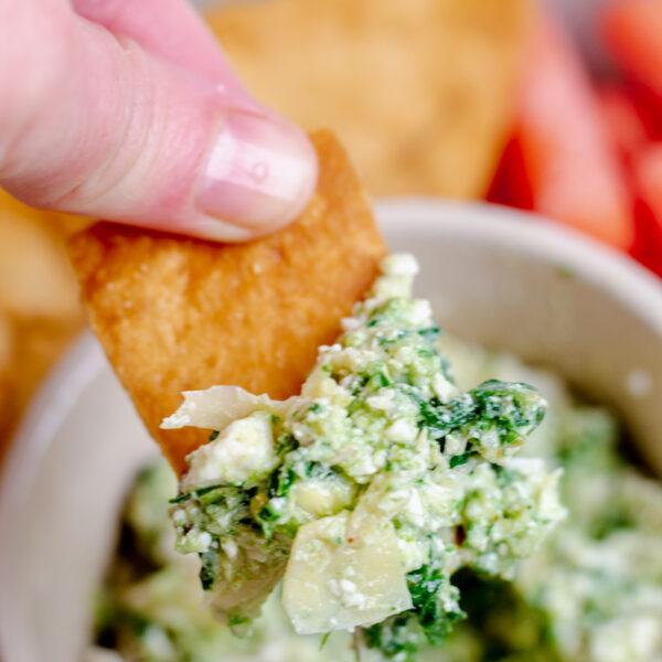 non descript hand dipping a pita chip into spinach artichoke feta dip