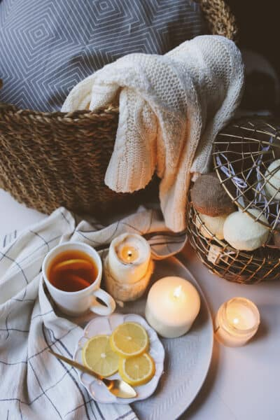 cozy setting of mug of tea, candles, lemon slices, and a wicker basket full of blankets
