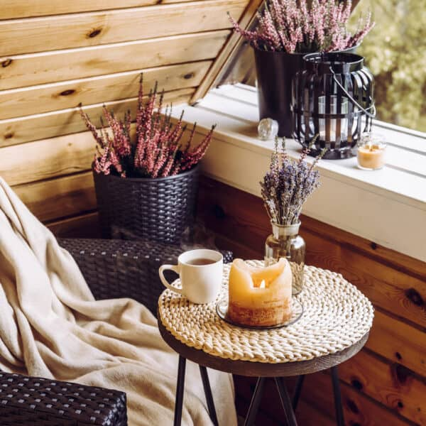 cozy reading nook with wicker chair, table, coffee cup, flowers, and candles