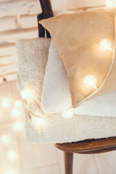 blankets and pillows on a wooden chair with warm string lights