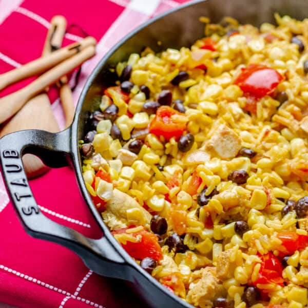 Staub pan with southwest chicken and rice on a red and white checkered placemat