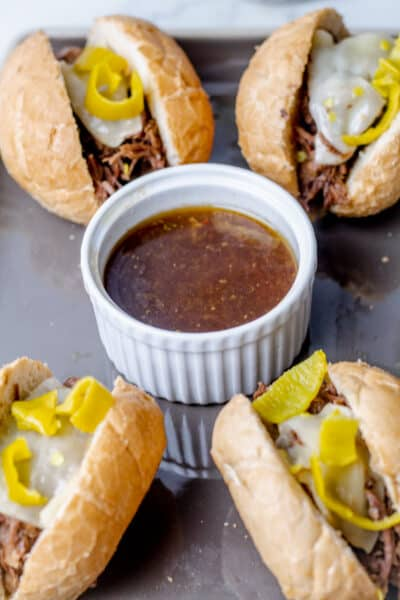 4 chicago style italian beef sandwiches surrounding a bowl of au jous