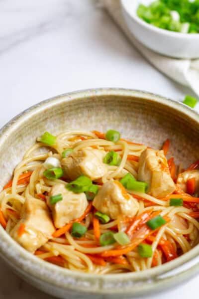 bowl of quick and easy spicy chicken lo mein with bowl of green onions in the background