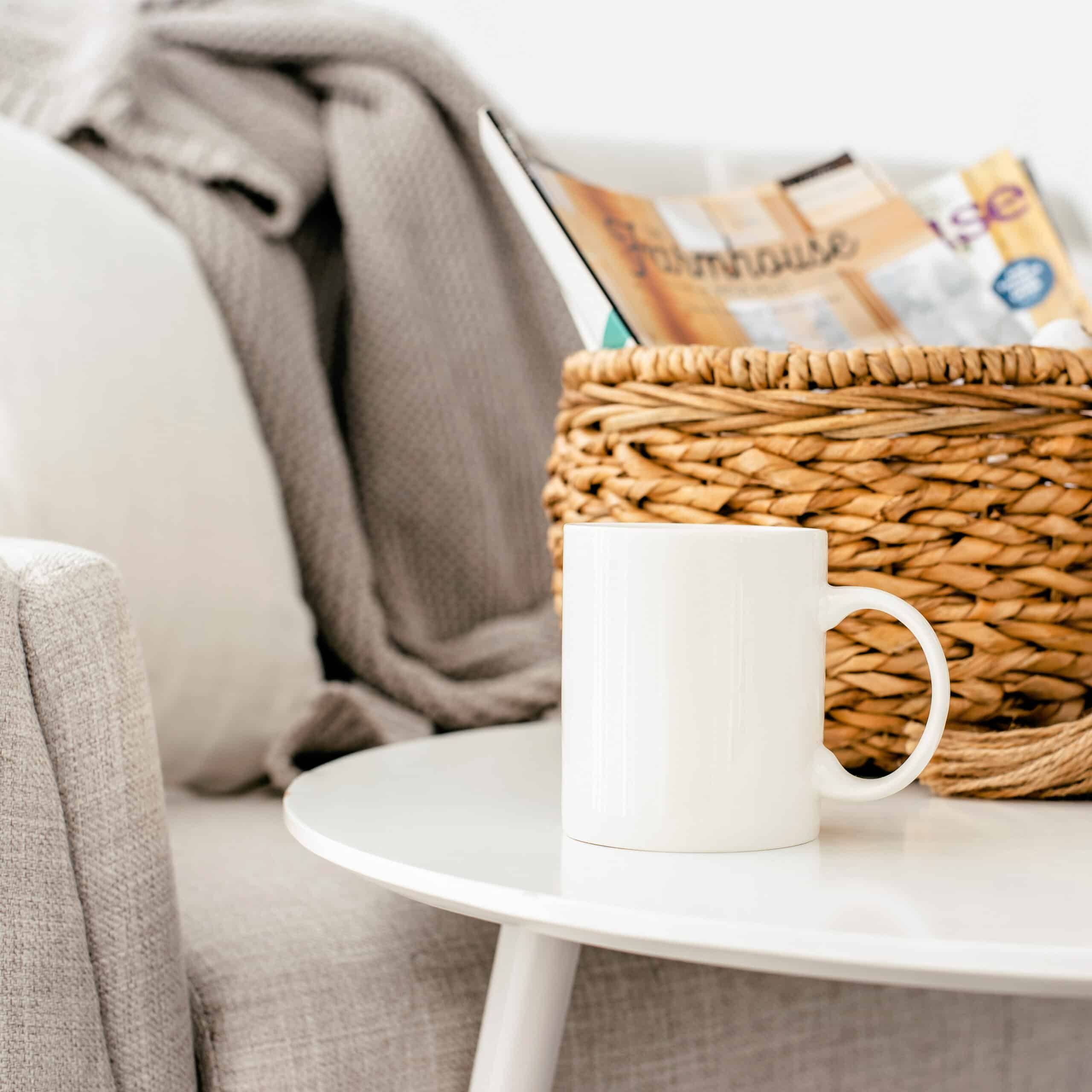 cozy living room with a couch, small table, basket of magazines, and a coffee cup