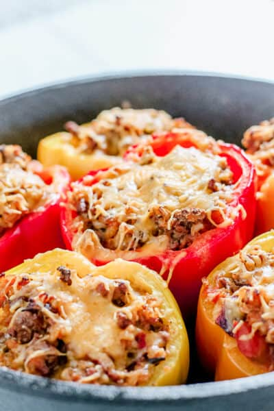 close up of red and yellow ground beef stuffed bell peppers in a cast iron pan