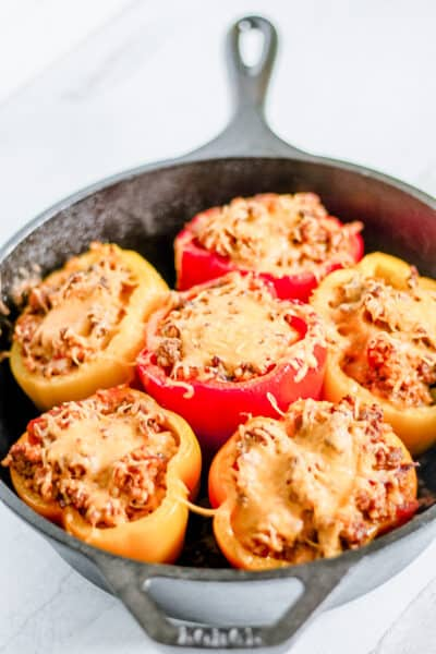 cast iron pan filled with 5 ground beef stuffed bell peppers topped with cheese