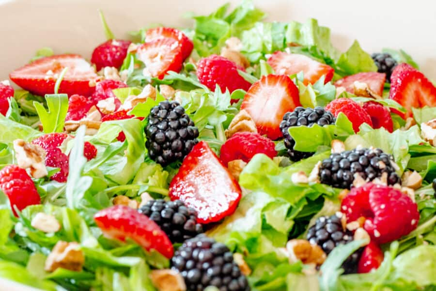 extreme close up of a bowl of summer berry salad with spring mix