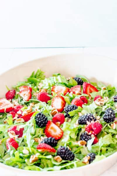 close up of a bowl of summer berry salad with lettuce
