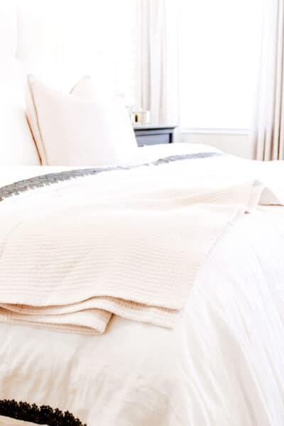 cozy bed with layers of blankets and pillows