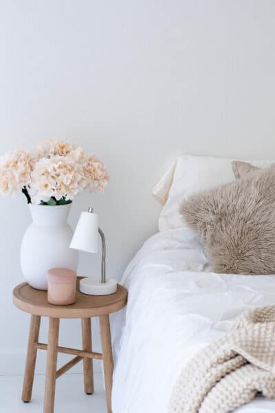 bed with throw pillows and a blanket next to a nightstand with flowers and a small lamp