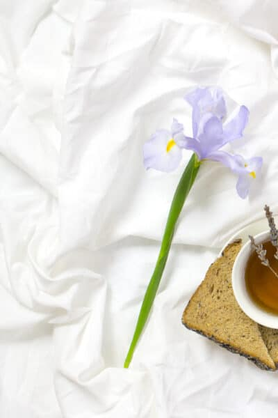 cup of tea and toast with a single flower on a bed