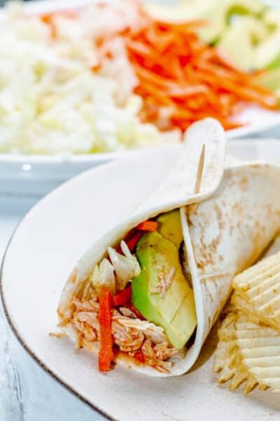 buffalo chicken wrap and potato chips on a white plate