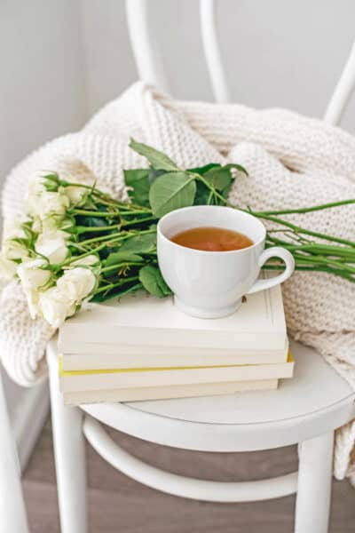 cup on tea and roses setting on top a pile of books on a chair