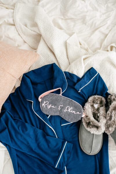 robe, slippers, and sleep mask on a messy bed