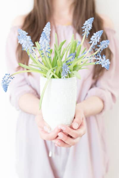 non descript woman holding out a vase of wildflowers
