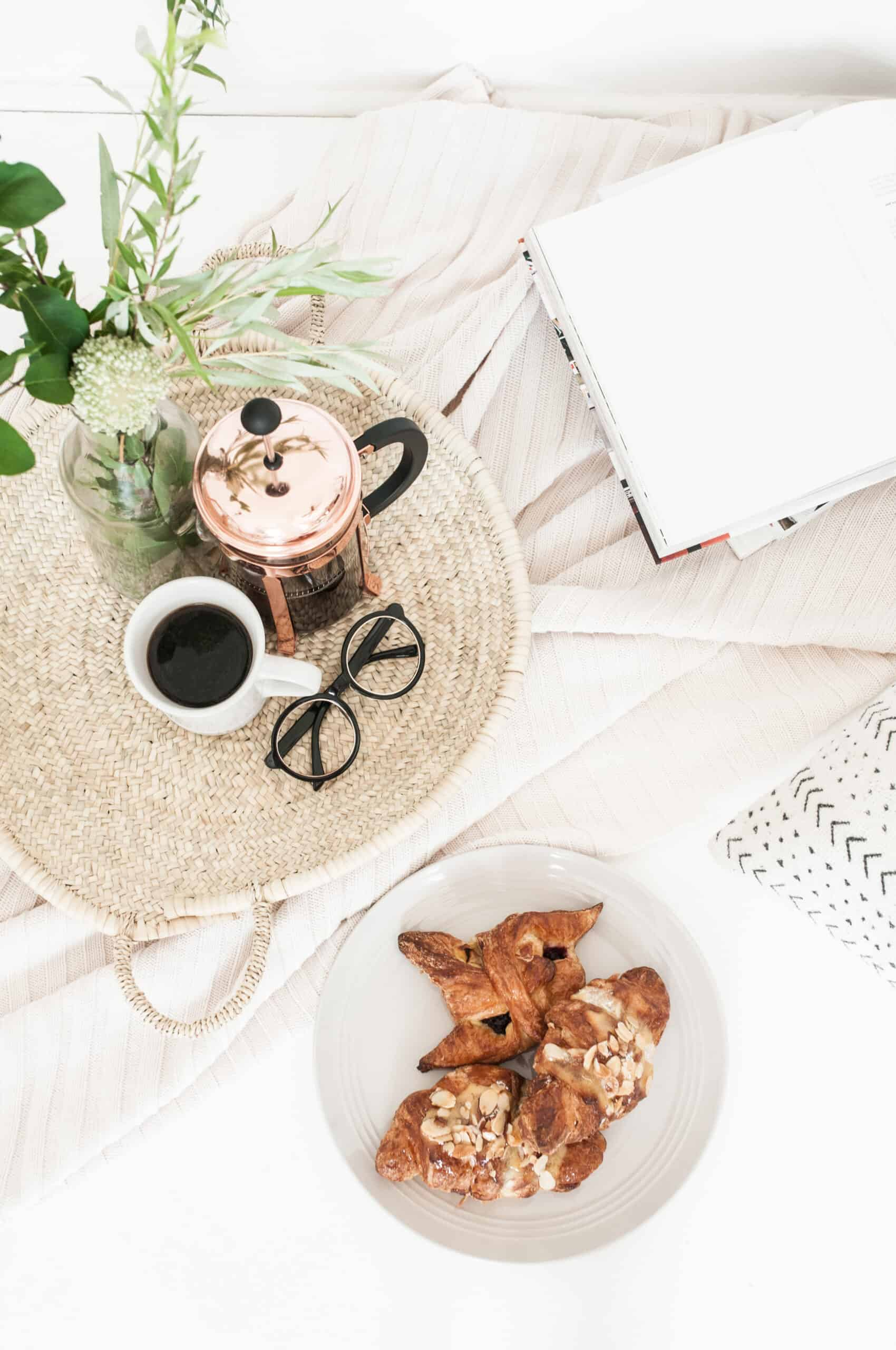 cozy scene of coffee, pastry, flowers and a closed pc