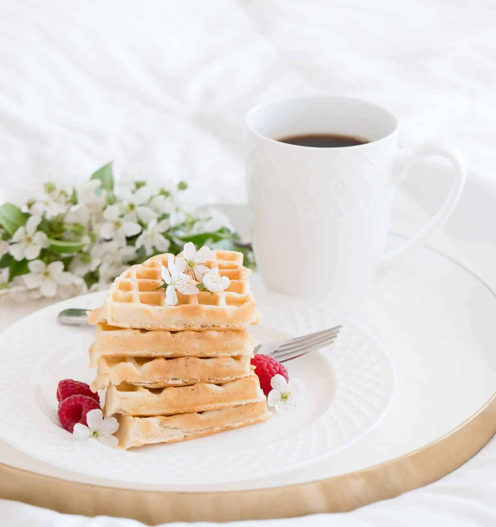 Plate with waffles and strawberries along with a cozy cup of coffee