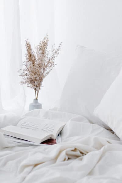 unmade cozy bed with a book