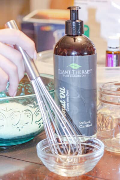 non descript hand whisking liquid ingredients for lavender and ylang ylang bath saltsd