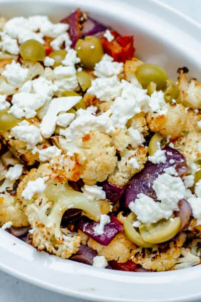 Serving pan with roasted Mediterranean Roasted Cauliflower, olive, feta, and red onions