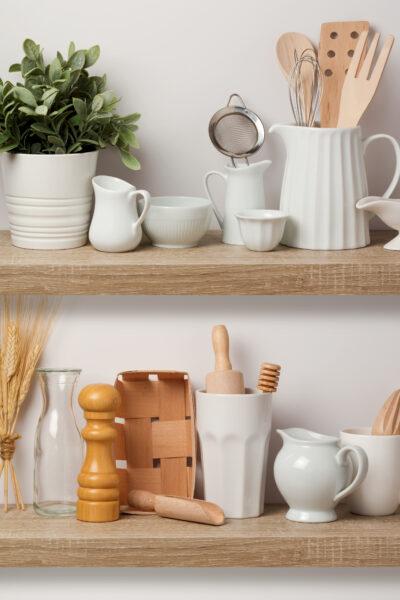 Kitchen utensils and dishware on wooden shelf. Kitchen interior background