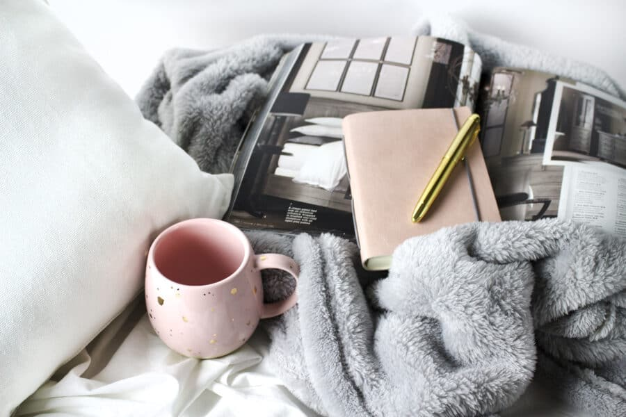 Hygge scene with books, fur blanket, fluffy pillow, and mug